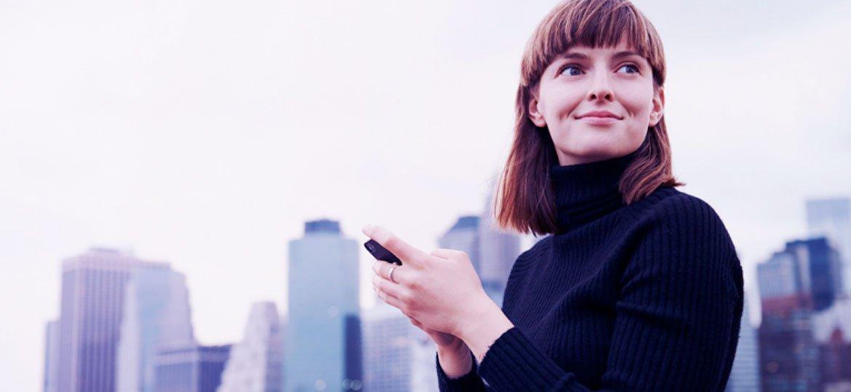 Mulher numa cidade grande usando o smartphone