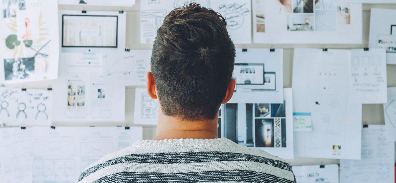 Homem olhando para uma parede com vários papéis colados