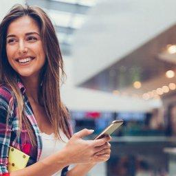 Mulher sorrindo no shopping com sacolas de compra e smartphone