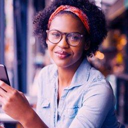 Mulher de óculos e bandana usando smartphone