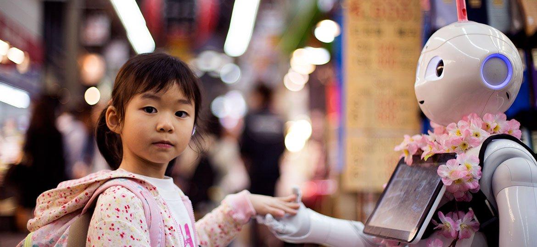 Menina segurando a mão de um robô sorridente
