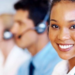 Equipe de atendimento ao cliente, mulher na frente sorrindo para a tela