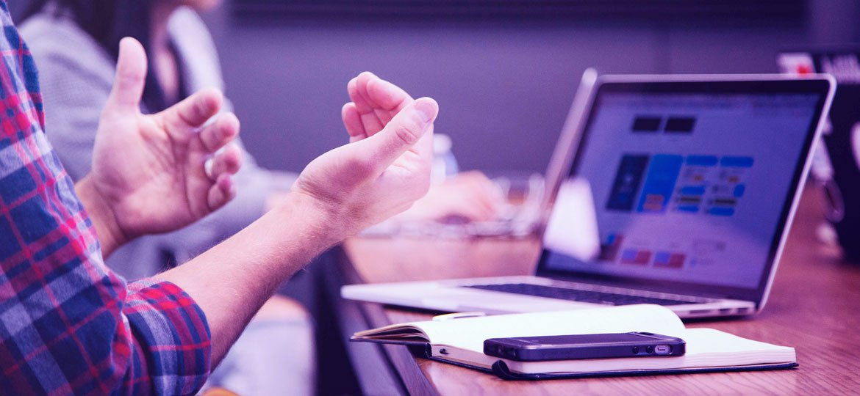 Homem gesticulando em frente ao notebook