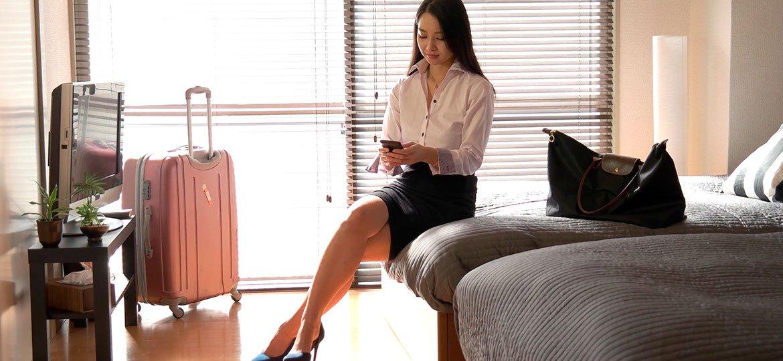 Executiva sentada na cama do hotel, com malas ao seu redor, usando seu smartphone