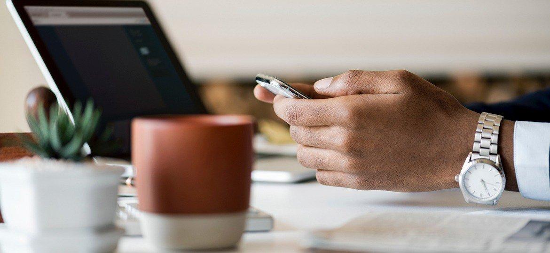 Homem de negócios usando smartphone em sua mesa de trabalho