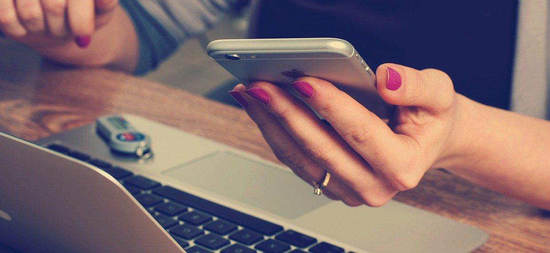 Mulher usando seu smartphone em frente ao notebook