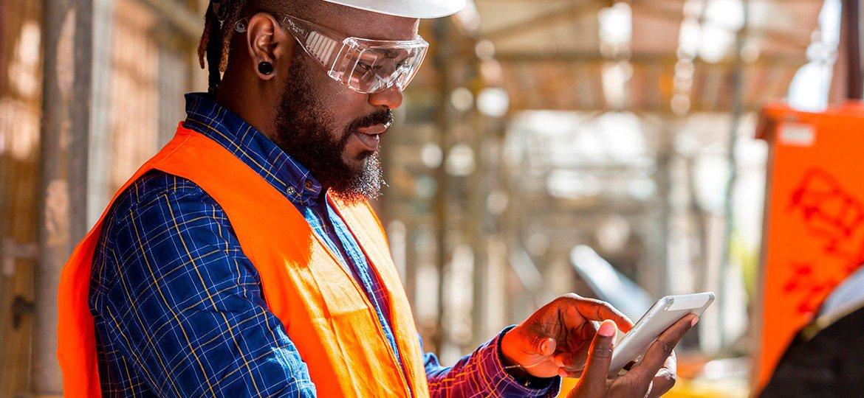 Engenheiro civil usando o seu smartphone na obra