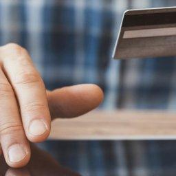 Homem fazendo uma compra online em seu tablet, segurando o cartão de crédito