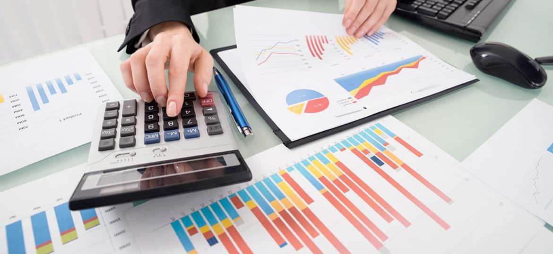 Mulher trabalhando em um escritório, cercada de gráficos, usando uma calculadora, para diminuir a inadimplência dos clientes