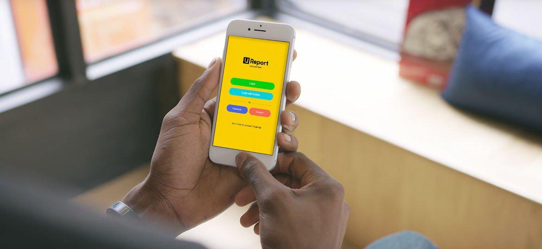 Homem segurando celular com o U-report na tela