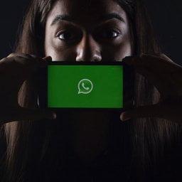 Mulher segurando smartphone em frente a boca, em fundo escuro, com a marca do whatsapp na tela