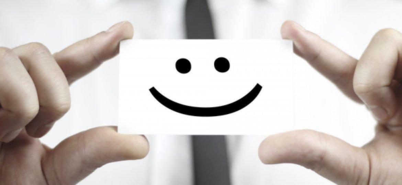 Homem segurando cartão com sorriso desenhado