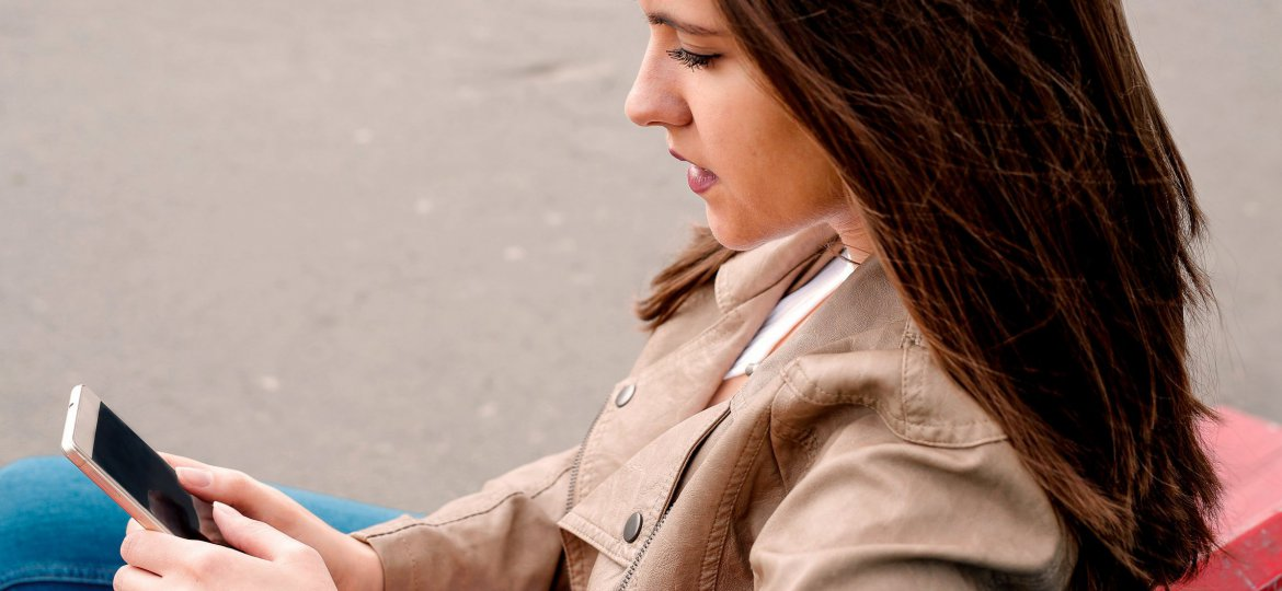 woman-in-brown-jacket-holding-smartphone-3768599